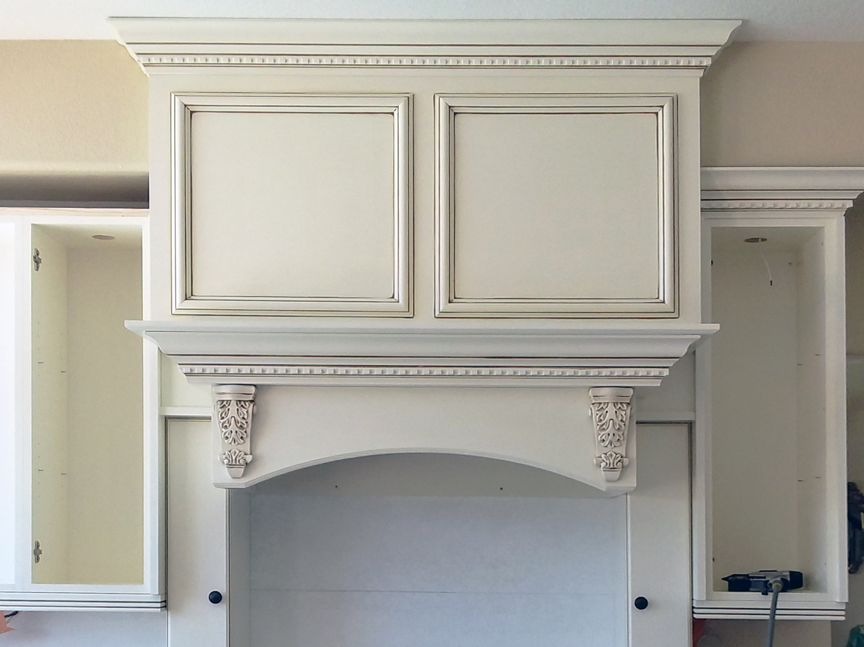 Image of a US RTA project in process showing a custom antique white hood and mantle