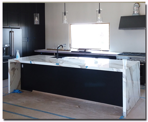 Custom black shaker cabinets with waterfall island countertops